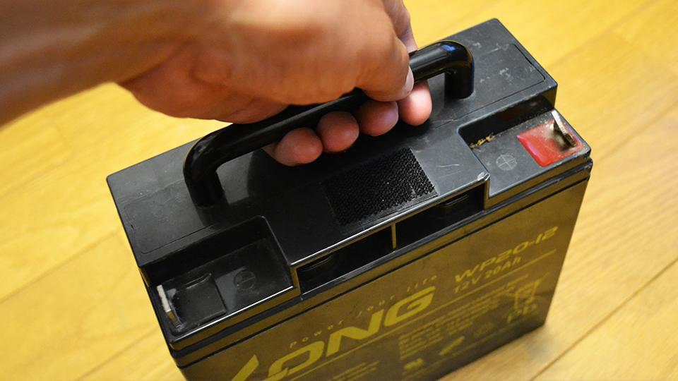 バッテリーの取っ手を掴む手
